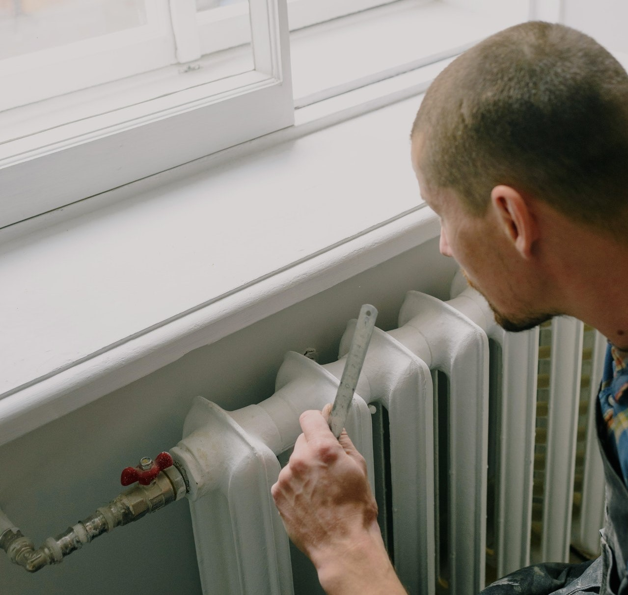Repairman performing commercial gas maintenance on a radiator